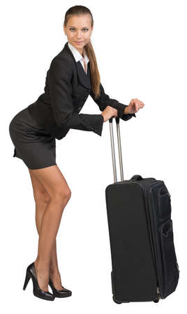 bending forward: Businesswoman bending forward leaning on extended handle of wheeled suitcase, looking at camera. Isolated over white background Stock Photo