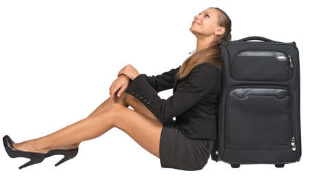 Businesswoman sitting next to front view suitcase, looking upwards, smiling. Isolated over white background photo