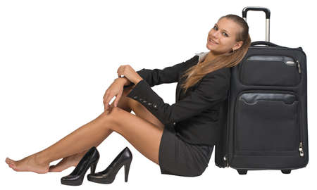 Businesswoman with her shoes off sitting next to front view suitcase with extended handle, looking at camera, smiling. Isolated over white background photo