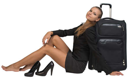 Businesswoman with her shoes off sitting hand resting on the floor, next to front view suitcase with extended handle, looking at camera. Isolated over white background photo