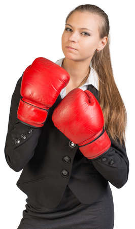 muffle: Businesswoman wearing boxing gloves standing in boxing stance, giving tough look at camera. Isolated over white background Stock Photo