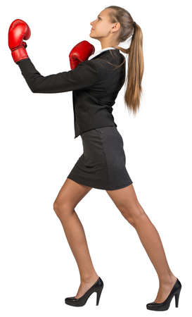 to muffle: Businesswoman wearing boxing gloves punching. Isolated over white background