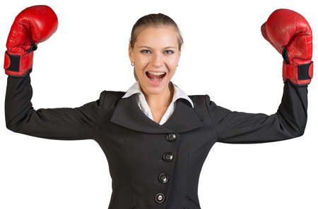 to muffle: Businesswoman wearing boxing gloves standing in victory pose, looking at camera, shouting. Isolated over white background