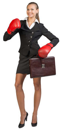 Businesswoman wearing boxing gloves holding briefcase, smiling, looking at camera. Isolated over white background photo