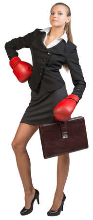 half turn: Businesswoman wearing boxing gloves holding briefcase, standing akimbo, looking at camera. Isolated over white background