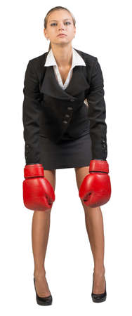 leaning forward: Businesswoman wearing boxing gloves, leaning forward with her hands straight down, looking at camera. Isolated over white background