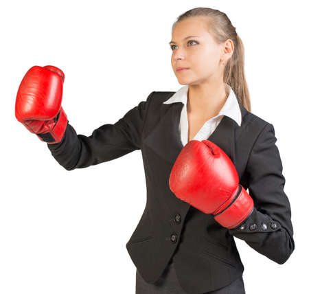 half turn: Businesswoman wearing boxing gloves standing in boxing stance. Isolated over white background