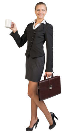 Businesswoman holding white mug at distance and briefcase, looking at camera, smiling. Isolated over white background photo