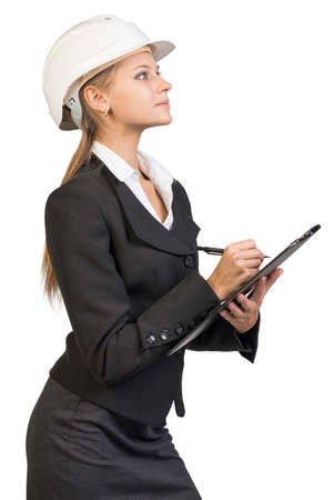 hard work ahead: Businesswoman wearing hard hat, writing on clipboard, looking ahead. Isolated over white background Stock Photo