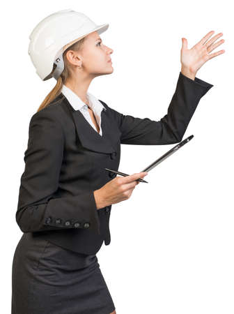 hard work ahead: Businesswoman wearing hard hat, with clipboard and pen, pointing at something, peering at it. Isolated over white background