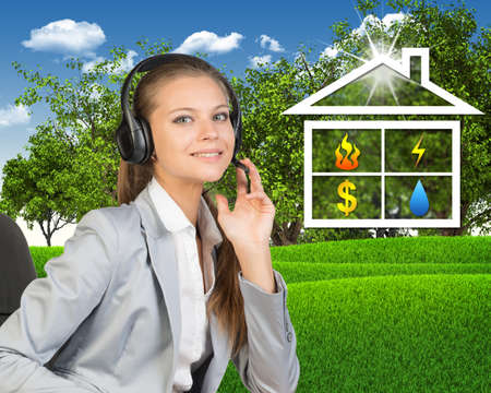 Businesswoman in headset, sitting on chair, her hand on microphone, looking at camera, smiling. Symbols of public utilities in house-shaped frame beside. Green hills and trees as backdrop photo