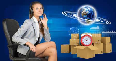 horisontal: Businesswoman in headset, sitting on office chair, her hand on microphone, sitting, looking at camera, smiling. Beside are commodity boxes with alarm-clock on top of one. Globe with horisontal rings, graphs and other virtual elements as backdrop.