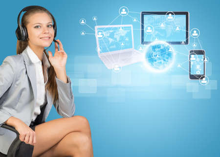 Businesswoman in headset, sitting on office chair, her hand on microphone, looking at camera, smiling. Globe, Network with people icons, laptop, tablet PC and smartphone beside, on light blue background photo