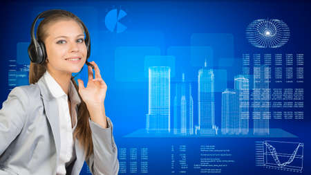 Businesswoman in headset, her hand on microphone, looking at camera, smiling. Wire-frame skyscrapers with hi-tech graphs and various data beside, on blue photo