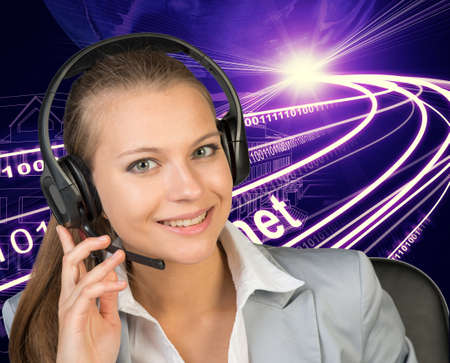 half turn: Closeup of businesswoman in headset, her hand on microphone, looking at camera, smiling. Wire-frame building with light as backfrop Stock Photo