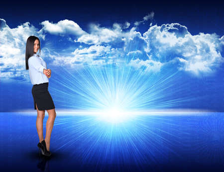 half turn: Businesswoman standing against digitally generated spacy blue landscape with rising sun and cloudy sky, looking at camera Stock Photo