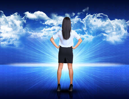 akimbo: Businesswoman standing akimbo against digitally generated spacy blue landscape with rising sun and cloudy sky