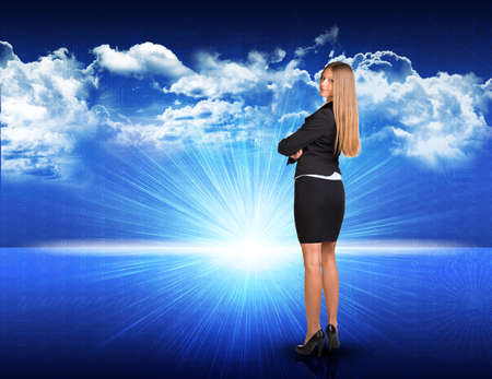 half turn: Businesswoman standing against digitally generated spacy blue landscape with rising sun and cloudy sky, looking back over her shoulder