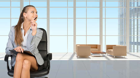 vast: Businesswoman in headset holding clipboard and pen, sitting on office chair in vast white interior with transparent wall, smiling