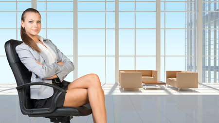 vast: Businesswoman in headset sitting on office chair with her arms crossed, in vast white interior with transparent wall, looking at camera, smiling Stock Photo