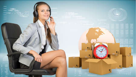 Businesswoman in headset, sitting on office chair, her hand on microphone, sitting, looking at camera, smiling. Beside are globe, commodity boxes and alarm-clock on top of one. Graphs and other virtual elements as backdrop. Element of this image furnished photo