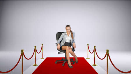 Businesswoman sitting on office chair standing on red carpet strip with gold stanchions, looking at camera, on white background photo