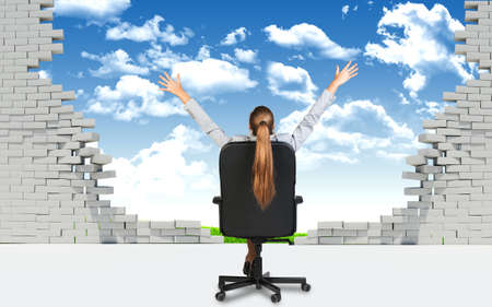 brick work: Businesswoman sitting on the office chair with her hands outstretched, in front of broken wall with blus sky and green field behind it.