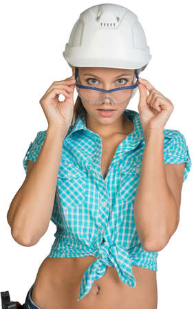Woman wearing hard hat looking at camera over protective glasses. Isolated on white background Stock Photo