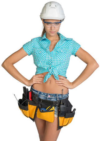 protective glasses: Woman in hard hat, tool belt and protective glasses standing akimbo, looking at camera. Isolated on white background