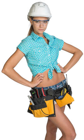 half turn: Woman in hard hat, tool belt and protective glasses standing akimbo, looking at camera. Isolated on white background