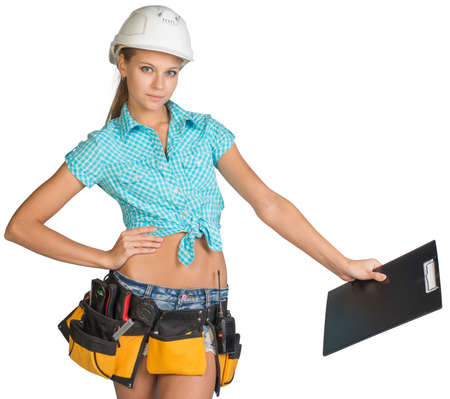 Woman in hard hat and tool belt standing akimbo, holding clipboard down at distance, looking at camera. Isolated on white background Stock Photo