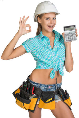 Woman in hard hat and tool belt showing calculator, making okay gesture, looking at camera, smiling. Isolated on white background photo