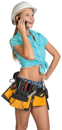 mani sui fianchi: Donna in cappello duro e strumento di cintura in piedi akimbo, chiamata sul cellulare, guardando in alto. Isolato su sfondo bianco