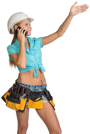 half turn: Woman in hard hat and tool belt calling on mobile phone, with her other hand showing direction, smiling. Isolated on white background