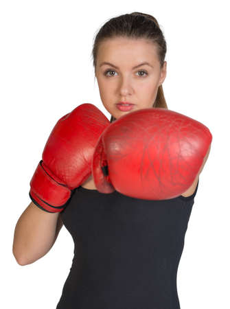 to muffle: Woman in boxing gloves, in punching pose, looking at camera. Isolated on white background Stock Photo