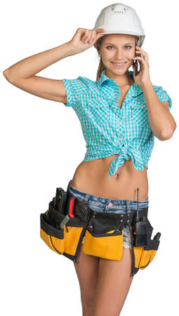 Woman in hard hat and tool belt calling on mobile phone, looking at camera. Isolated on white background photo