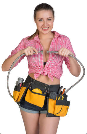 Woman in tool belt holding flexible tap hose, looking at camera, smiling. Isolated on white background