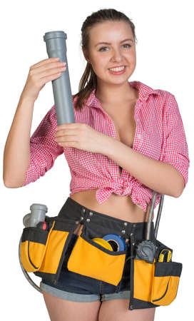Woman in tool belt holding fitting pipe, looking at camera, smiling. Isolated on white background photo