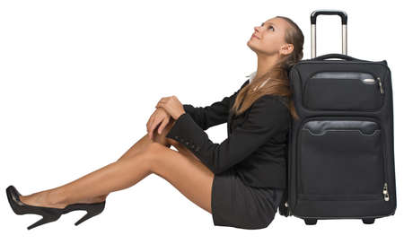 Businesswoman sitting next to front view suitcase with extended handle, looking upwards. Isolated over white background photo