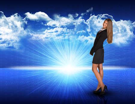 loose hair: Imprenditrice in piedi contro generato digitalmente spacy paesaggio blu con sole che sorge e cielo nuvoloso, guardando indietro sulla sua spalla, sorridente