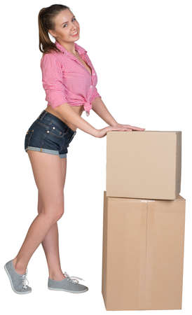 half turn: Woman leaning on two stacked cardboard boxes, looking at camera, smiling. Isolated on white background