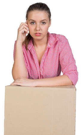 Woman leaning on cardboard box, looking at camera. Isolated on white background photo