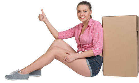 all right: Woman sitting next to cardboard box, giving thumb up, looking at camera, smiling. Isolated on white background Stock Photo