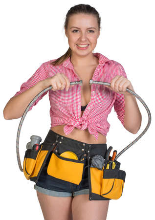 braided flexible: Woman in tool belt holding flexible tap hose, looking at camera, smiling. Isolated on white background