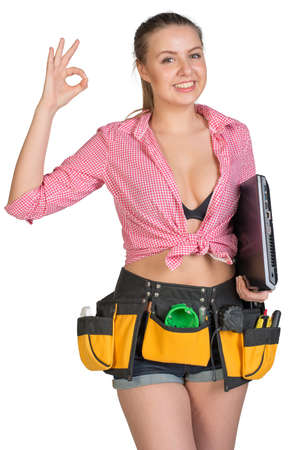 Woman in tool belt, with laptop under her armpit, showing okay sign, looking at camera, smiling. Woman in tool belt holding laptop under her armpit, smiling. Isolated on white background photo