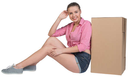 half turn: Woman sitting next to cardboard box, looking at camera, smiling. Isolated on white background