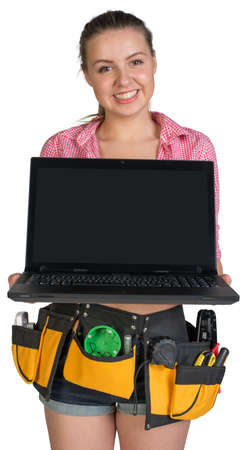 Woman in tool belt showing opened laptop with blank screen, looking at camera, smiling. Isolated on white background photo