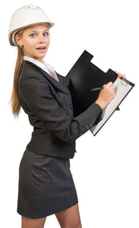half turn: Businesswoman wearing hard hat, writing on clipboard, looking at camera. Isolated over white background