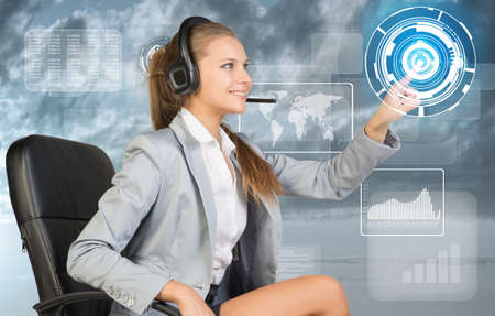 Businesswoman in headset sitting on chair using virtual interface. World map, graphs and figures over cloudy sky as backdrop photo