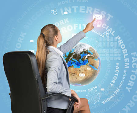 Businesswoman sitting on chair pressing envelope icon on virtual interface. Globe with virtual elements and words related to business as backdrop. photo